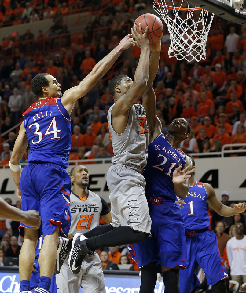 Photo - Oklahoma State's Marcus Smart (33) goes to the basket between Kansas' Perry Ellis (34) and Kansas' Joel Embiid (21) during late in an NCAA college basketball game between Oklahoma State University (OSU) and the University of Kansas at Gallagher-Iba Arena in Stillwater, Okla., Saturday, March 1, 2014. Oklahoma State won 72-65. Photo by Bryan Terry, The Oklahoman