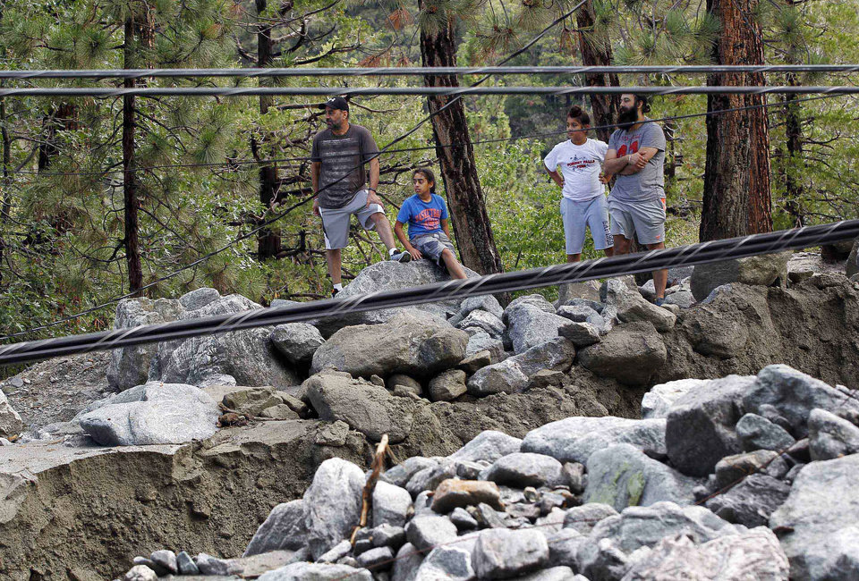 Photo - Onlookers view rocks and mud and downed power lines from a mudslide in the mountain community of Forest Falls in the San Bernardino Mountains Monday, Aug. 4, 2014. Crews cleared roads in an area where some 2,500 had been stranded after thunderstorms caused mountain mudslides in Southern California over the weekend, while authorities estimated that between six and eight homes were badly damaged and likely uninhabitable. One person was found dead in a vehicle that was caught in a flash flood. A group of campers spent the night at a community center near Forest Falls. (AP Photo/Nick Ut)