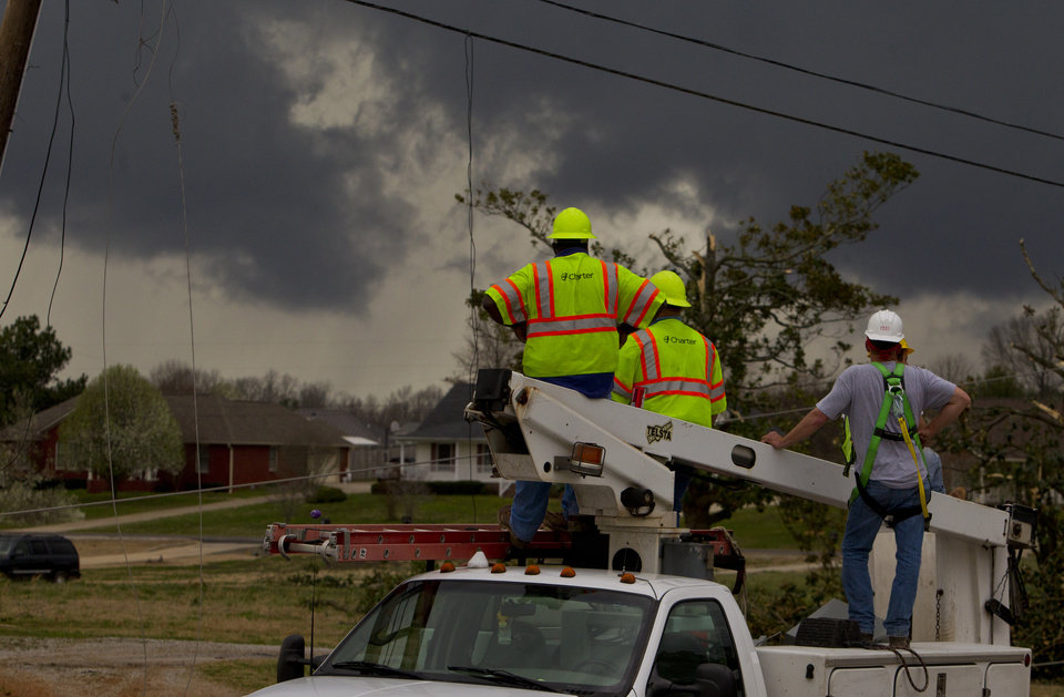 Charter cable workers keep a close eye on an approaching storm as sirens sound signaling a possible tornado on Friday, March. 2, 2012, in Athens, Ala.  (AP Photo/Butch Dill) ORG XMIT: ALBD106