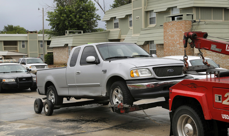 Photo -  The truck in which two people were shot Wednesday is removed from a northwest Oklahoma City apartment complex by a wrecker. Photo by Jim Beckel, The Oklahoman   Jim Beckel