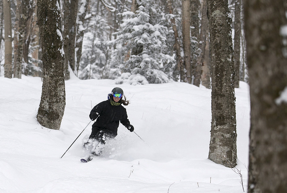 Photo - In this Feb. 10, 2014 photo provided by Killington Resort, a skier glides in the Natural Woods area of the ski resort in Killington, Vt.  As part of an effort to keep skiers in bounds and avoid expensive rescue operations that can involve dozens of people, Killington opened 745 acres of terrain designed to give skiers a safer back country experience. The 745-acre Natural Area on Killington peak allows the skiers and riders to get the back-country experience in the ungroomed areas between the trails, but when skiers and riders head downhill they will end up back at the base lodges. (AP Photo/Killington Resort, Chandler Burgess)