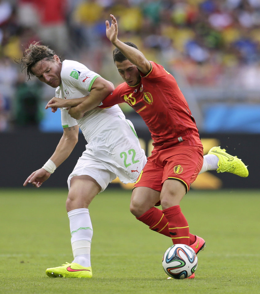 Photo - Algeria's Mehdi Mostefa, left, holds on to Belgium's Eden Hazard during the group H World Cup soccer match between Belgium and Algeria at the Mineirao Stadium in Belo Horizonte, Brazil, Tuesday, June 17, 2014.  (AP Photo/Petr David Josek)