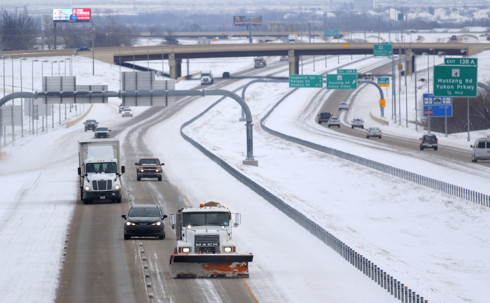 Photo - A snow plow clears a section of I-40 in Yukon, Friday January, 6 2017. Photo By Steve Gooch, The Oklahoman