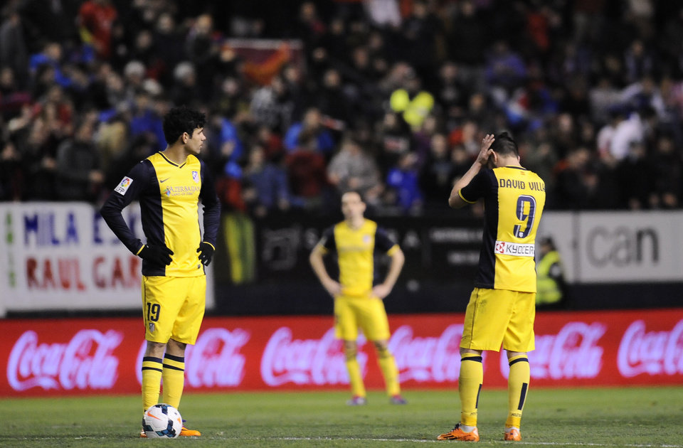 Photo - Atletico de Madrid's Diego Costa of Brazil, left, and David Villa, tight, react  during their Spanish League soccer match, at El Sadar stadium in Pamplona, Spain, Sunday, Feb. 23, 2014. Atletico de Madrid lost the match 3-0. (AP Photo/Alvaro Barrientos)