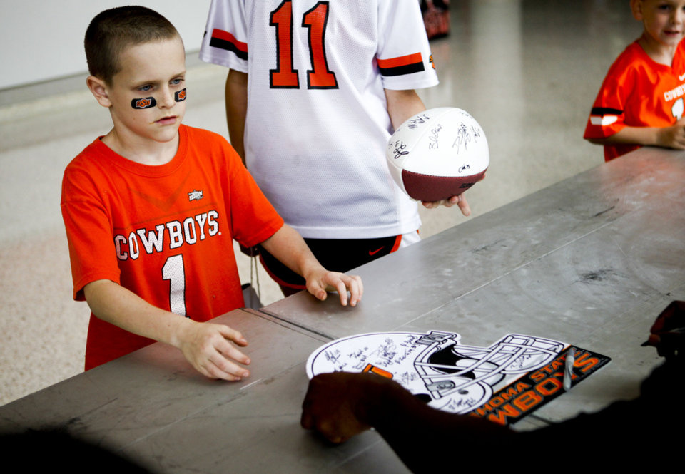 Brandon Roberts, 9, of Enid, Okla., has a poster signed by football players at fan appreciation day at Gallagher-Iba Arena in Stillwater on August 3, 2013. KT King, For The Oklahoman