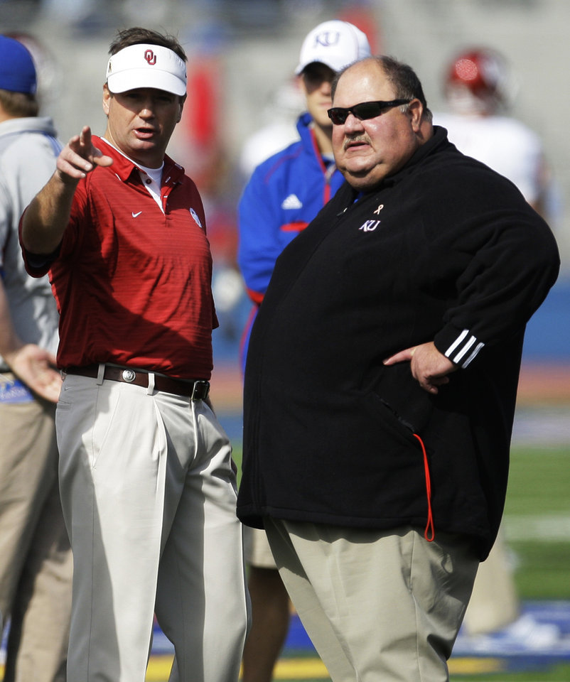 Photo - UNIVERSITY OF OKLAHOMA / OU: Oklahoma coach Bob Stoops, left, and Kansas coach Mark Mangino talk before their NCAA college football game Saturday, Oct. 24, 2009, in Lawrence, Kan. (AP Photo/Orlin Wagner) ORG XMIT: KSOW106