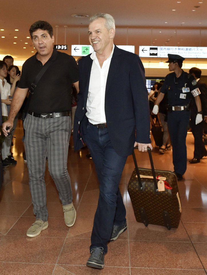 Photo - Japan's new national team coach Javier Aguirre of Mexico, center, arrives at Haneda airport in Tokyo, Monday, Aug. 11, 2014. The 55-year-old Aguirre will take the reins for the Japanese side, with his first match at the helm starting with a friendly against Uruguay at Sapporo Dome on Sept. 5. (AP Photo/Kyodo News) JAPAN OUT
