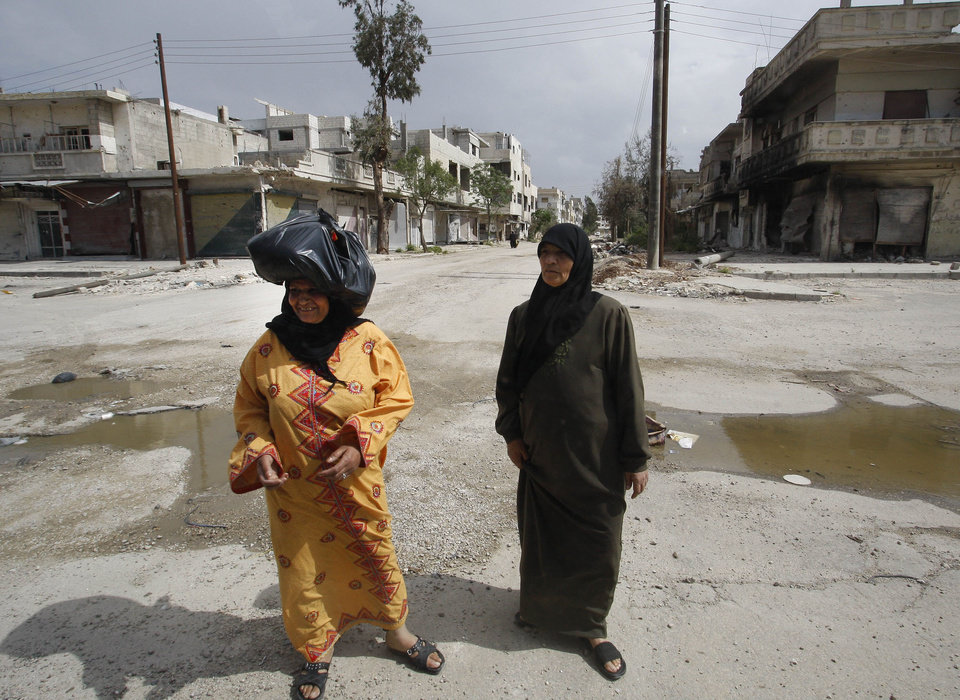 Photo -   In this picture taken during a UN observer-organized tour, Syrian women walk in an empty street in front of destroyed shops during the UN observers' visit to Homs city, central Syria, on Thursday, May 3, 2012. Syrian security forces stormed dorms at a northwestern university to break up anti-government protests there, killing at least four students and wounding several others with tear gas and live ammunition, activists and opposition groups said Thursday. (AP Photo/Muzaffar Salman)