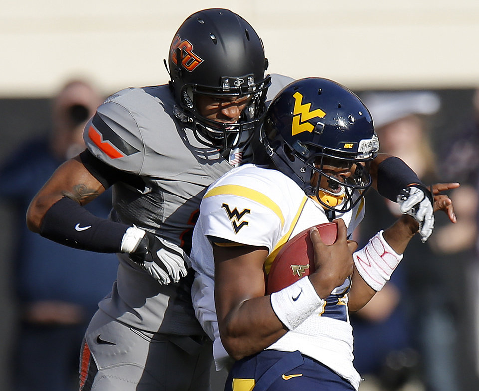 Photo - Oklahoma State's Lyndell Johnson (27) brings down West Virginia's Geno Smith (12) during a college football game between Oklahoma State University (OSU) and West Virginia University at Boone Pickens Stadium in Stillwater, Okla., Saturday, Nov. 10, 2012. Photo by Bryan Terry, The Oklahoman