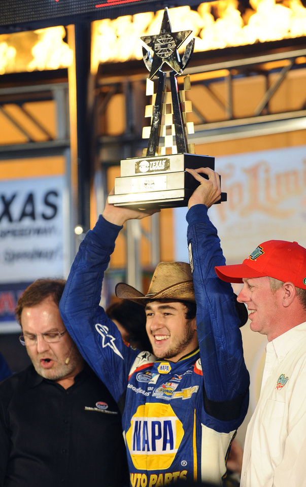Photo - Chase Elliott holds up the trophy in Victory Lane after winning the NASCAR Nationwide Series auto race at Texas Motor Speedway in Fort Worth, Texas, Friday, April 4, 2014. (AP Photo/Ralph Lauer)