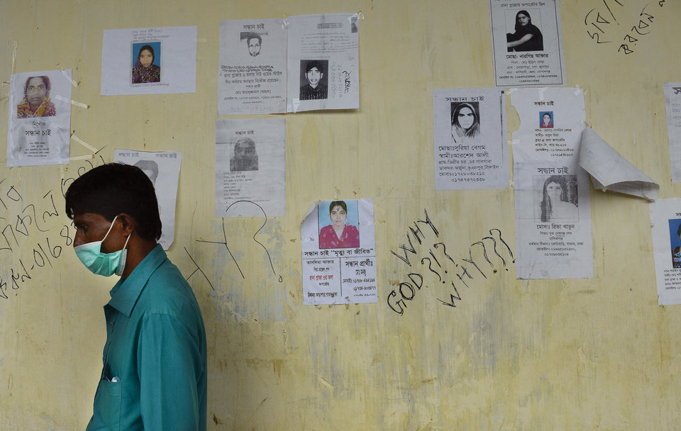 Photo - A Bangladeshi man walks past portraits of missing victims and graffiti written on the wall of a makeshift morgue in Savar, near Dhaka, Thursday, May 9, 2013. The death toll from the collapse of a garment factory building passed 900 on Thursday even as a fire in an 11-story garment factory Wednesday night in Dhaka killed eight people, including a ruling-party politician and a top official in the country's powerful clothing manufacturers' trade group. (AP Photo/Ismail Ferdous)