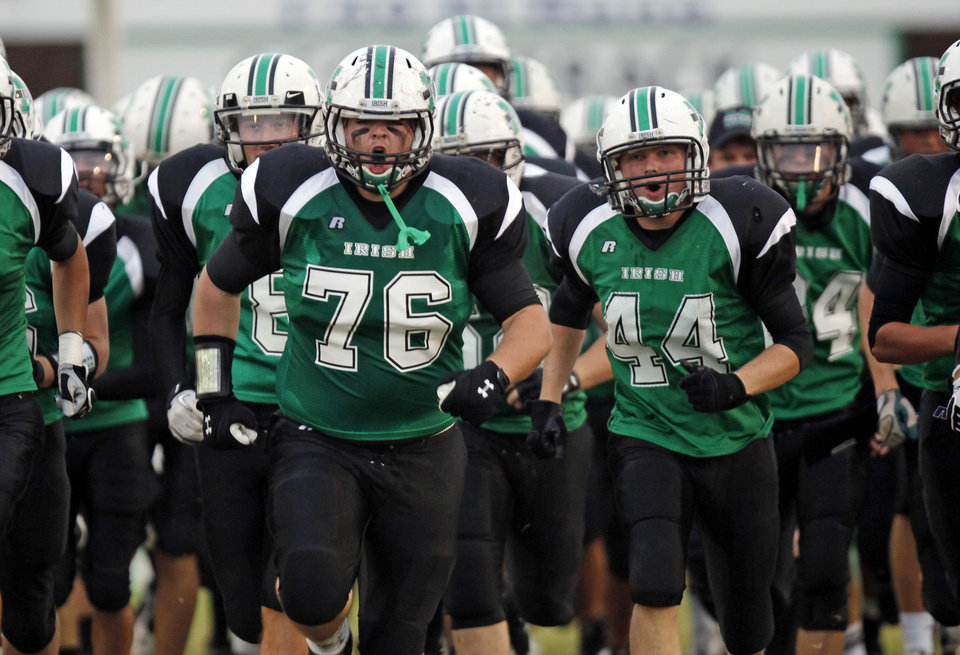 Photo - The Bishop McGuinness Fighting Irish, including Chip Daniel (76) and Jordan Edwards (44)  take the field before a high school football game between Millwood and Bishop McGuinness at Bishop McGuinness Catholic High School in Oklahoma City, Friday, Sept. 16, 2011. Photo by Nate Billings, The Oklahoman