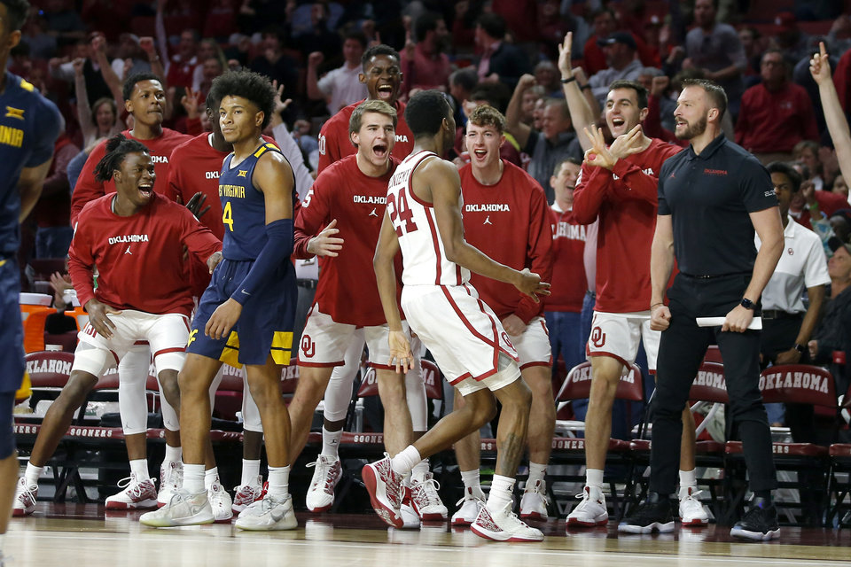 Photo - The Oklahoma bench celebrates after Oklahoma's Jamal Bieniemy (24) made a 3-pointer over West Virginia's Miles McBride (4) during an NCAA mens college basketball game between the University of Oklahoma Sooners (OU) and the West Virginia Mountaineers at the Lloyd Noble Center in Norman, Okla.,Saturday, Feb. 8, 2020. Oklahoma won 69-59. [Bryan Terry/The Oklahoman]