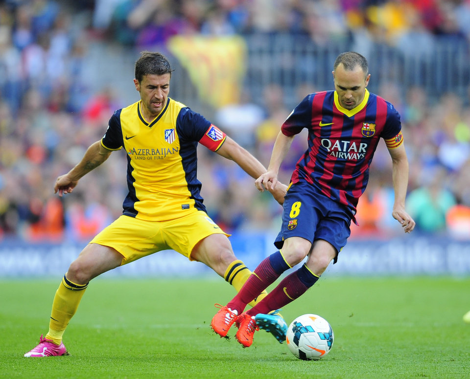 Photo - Atletico's Gabi, left, challenges for the ball Barcelona's Andres Iniesta during a Spanish La Liga soccer match between FC Barcelona and Atletico Madrid at the Camp Nou stadium in Barcelona, Spain, Saturday, May 17, 2014. (AP Photo/Manu Fernandez)