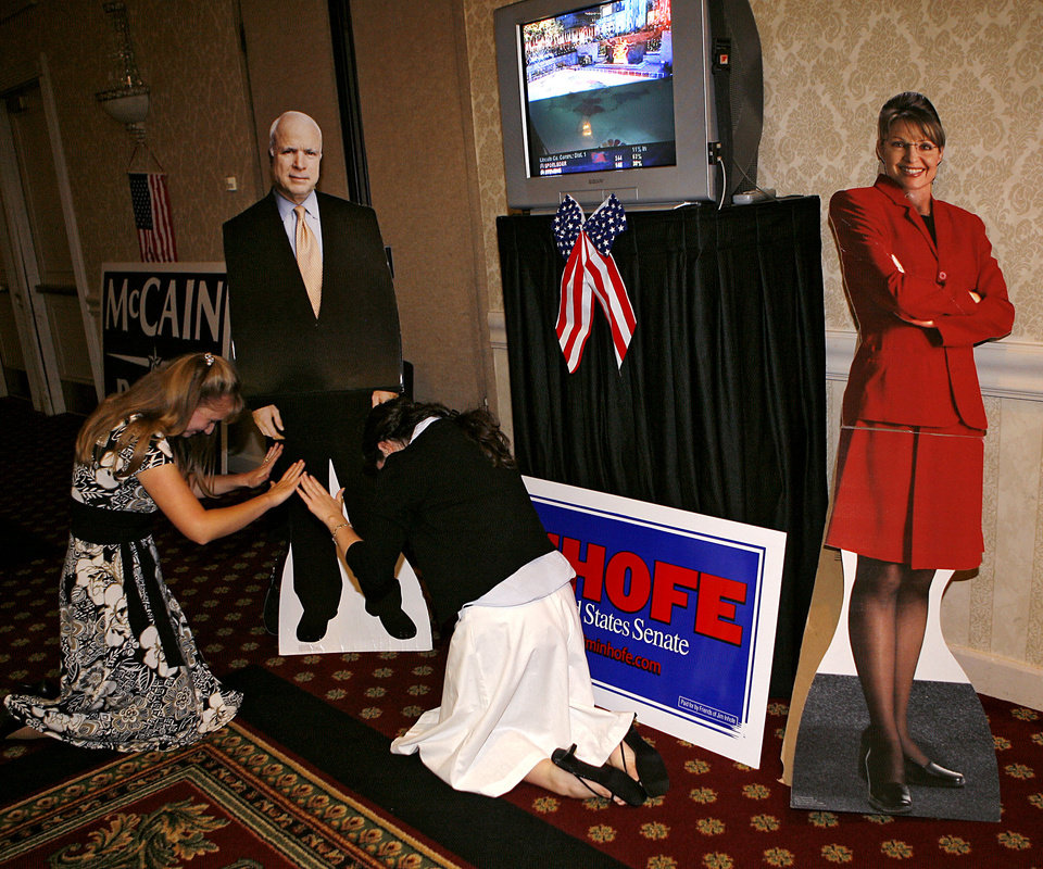 Photo - Lauree Beth Stedje (left) and Eden Bullock jokingly bow in front of a John McCain cardboard cutout, while the Sarah Palin Cutout sits in the corner during the Republican watch party at the Oklahoma City Marriott on Northwest Expressway in oklahoma City on Tuesday Nov. 4, 2008. By John Clanton, The Oklahoman