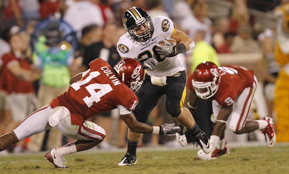 Photo - Oklahoma's Aaron Colvin tries to stop Missouri's T.J. Moe during their game Saturday in Norman. OU won 38-28. Photo by Chris Landsberger, The Oklahoman