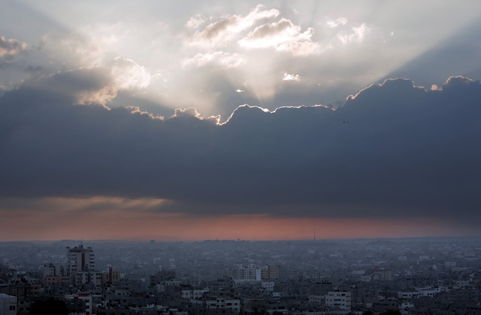 Photo - The sun rises over Gaza City, Sunday, Aug. 3, 2014. The Israeli military said Sunday that an Israeli soldier it previously believed had been captured by Hamas fighters in a Gaza ambush had in fact been killed in battle that day. The soldier's purported capture Friday had helped shatter an internationally brokered cease-fire, drawn global condemnation and triggered a military assault on the area of his disappearance in southern Gaza that left dozens of Palestinians dead and scores of homes destroyed.  (AP Photo/Khalil Hamra)