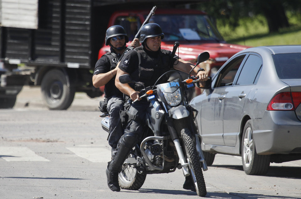 Photo - Police officers patrol the streets after looting on the outskirts of Buenos Aires, Friday, Dec. 21, 2012. Two people were killed in Argentina as looters ransacked supermarkets in several cities, officials said Friday. Santa Fe Province Security Minister Raul Lamberto said the incidents were not triggered by social protests but were simple acts of vandalism. (AP Photo/Natacha Pisarenko)