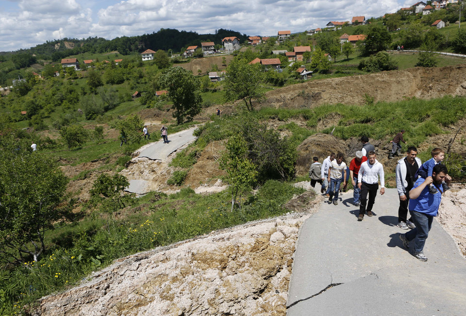 Photo - Bosnian people walk on a broken road after a landslide which swept away eight houses near Kalesija, Bosnia, 150 kms north of Sarajevo, Sunday May 18, 2014. Packed into buses, boats and helicopters, carrying nothing but a handful of belongings, tens of thousands fled their homes in Bosnia and Serbia, seeking to escape the worst flooding in a century. (AP Photo/Amel Emric)