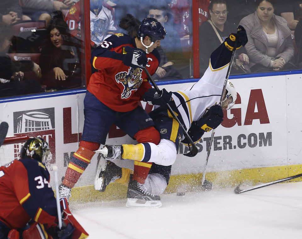 Photo - Florida Panthers' Ed Jovanovski (55) and Nashville Predators' Paul Gaustad (28) battle for the puck during the second period of a NHL hockey game in Sunrise, Fla., Saturday, Jan. 4, 2014. (AP Photo/J Pat Carter)