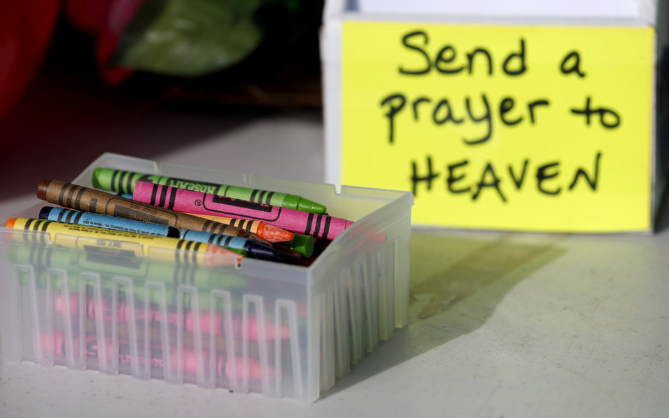 Photo - Crayons sit on a table outside of a barbershop a day after a gunman opened fire at Sandy Hook Elementary School, Saturday, Dec. 15, 2012, in the Sandy Hook village of Newtown, Conn.  The massacre of 26 children and adults at Sandy Hook Elementary school elicited horror and soul-searching around the world even as it raised more basic questions about why the gunman, 20-year-old Adam Lanza, would have been driven to such a crime and how he chose his victims.  (AP Photo/Julio Cortez) ORG XMIT: CTJC124