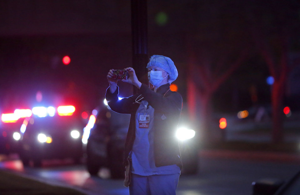 Photo - A person records a parade of emergency vehicles during a headlights and flashing lights for Hope at the Chidlren's Hospital in Oklahoma City, Friday, April 3, 2020. The Oklahoma City Police, Oklahoma City Fire Department, OU Police, EMSA, Oklahoma County Sheriffs and Oklahoma City Thunder mascot Rumble paraded around the OU Medical Center to show support for medical staff and patients at the of the Children's Hospital and the campus. [Sarah Phipps/The Oklahoman]