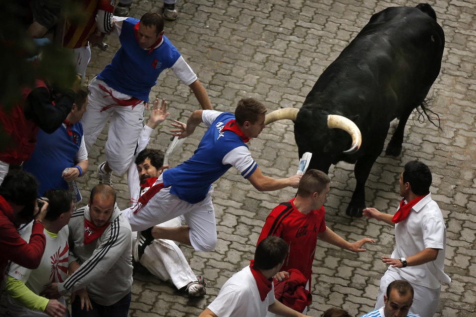 Photo - U.S. runner Bill Hillmann, 35, from Chicago, center left, falls seconds before a Victoriano del Rio ranch fighting bull gored him on his right leg during the running of the bulls of the San Fermin festival, in Pamplona, Spain, Wednesday, July 9, 2014. Revelers from around the world arrive in Pamplona every year to take part on some of the eight days of the running of the bulls glorified by Ernest Hemingway's 1926 novel
