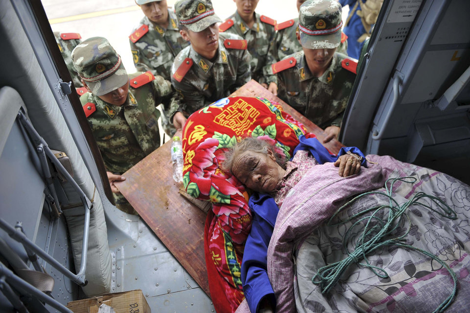 Photo - In this photo released by China's Xinhua News Agency, rescuers convey an injured person in the quake-hit Longtoushan Town of Ludian County in Zhaotong city, southwest China's Yunnan Province, Monday, Aug. 4, 2014.  Rescuers dug through shattered homes Monday looking for survivors of a strong earthquake in southern province as the death toll rose to hundreds of people, with more than a thousand injured.(AP Photo/Xinhua, Xue Yubin) NO SALES