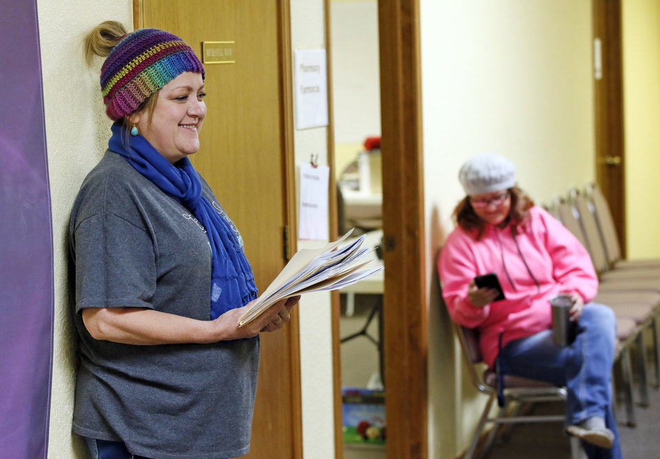 Photo -  Volunteer Angelia Howry, left, of Blanchard, waits to take patients to the next available doctor as Jamie Barker, of Lexington, waits to go into the pharmacy during the Hope Medical Clinic at the Slaughterville Baptist Church. [PHOTO BY NATE BILLINGS]