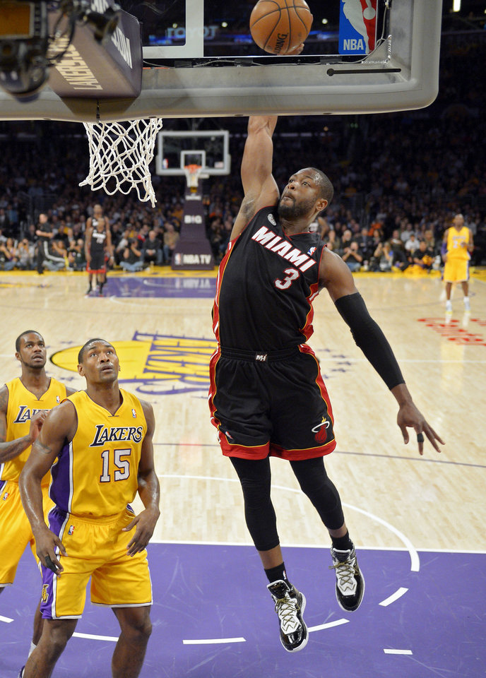 Miami Heat guard Dwyane Wade (3) dunks as Los Angeles Lakers forward Earl Clark, left, and forward Metta World Peace (15) watch during the first half of their NBA basketball game, Thursday, Jan. 17, 2013, in Los Angeles. (AP Photo/Mark J. Terrill)