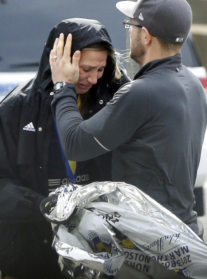 An unidentified Boston Marathon runner is comforted as she cries in the aftermath of two blasts which exploded near the finish line of the Boston Marathon in Boston, Monday, April 15, 2013. (AP Photo/Elise Amendola)  ORG XMIT: MAEA119