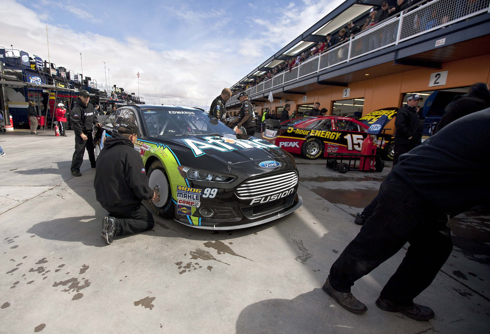 The pit crew for Carl Edwards prepares his No. 99 car for a template check before qualifying for the NASCAR Sprint Cup Series auto race, Friday, March 8, 2013 in Las Vegas.(AP Photo/Julie Jacobson)