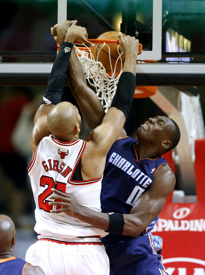 Photo - Chicago Bulls forward Taj Gibson, left, dunks the ball against Charlotte Bobcats center Bismack Biyombo, right, during the first half of an NBA basketball game in Chicago, Saturday, Jan. 11, 2014. (AP Photo/Kamil Krzaczynski)