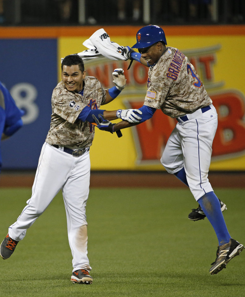 Photo - New York Mets Curtis Granderson, right, celebrates with the Mets Ruben Tejada (11) after Tejada hit an 11th-inning, game-winning, walk-off RBI single top lift the Mets to a 4-3 victory over the Atlanta Braves in a baseball game in New York, Monday, July 7, 2014. (AP Photo/Kathy Willens)