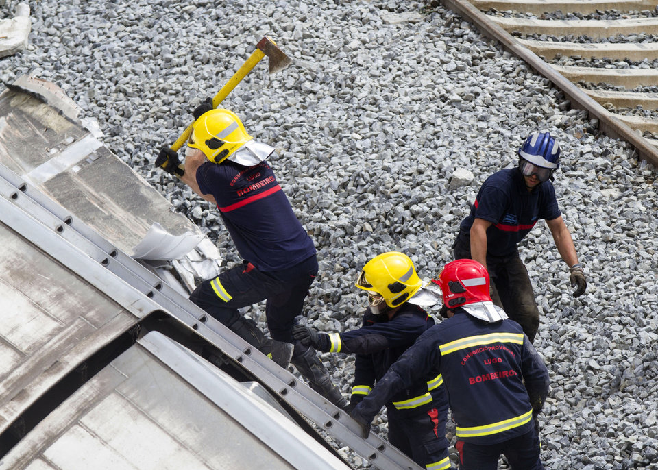Photo - A firefighter uses and axe to open their way inside a train car at the site of a train accident in Santiago de Compostela, Spain, on Thursday, July 25, 2013. An Associated Press analysis of video images shows that a Spanish train was traveling well above the speed limit when it derailed, killing at least 80 people. Officials say the speed limit on that section of track is 80 kph (50 mph). (AP Photo/Lalo Villar)