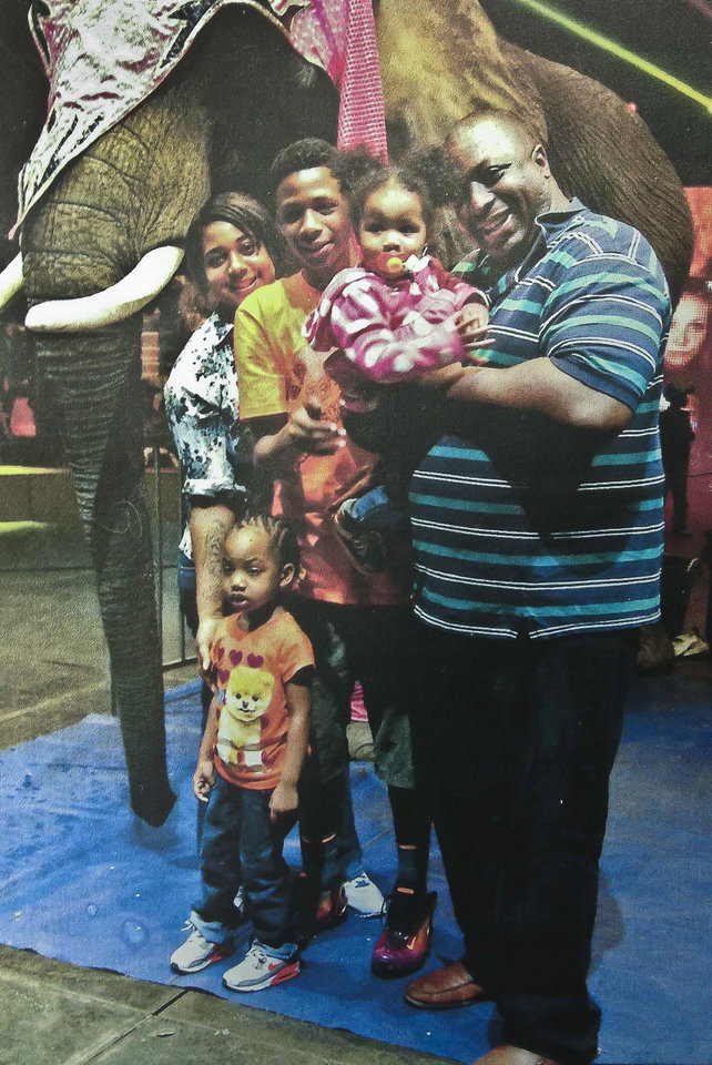 Photo - In this undated family photo provided by the National Action Network, Saturday, July 19, 2014, Eric Garner, right, poses with his children during during a family outing. Garner was confronted by police trying to arrest him on suspicion of selling untaxed, loose cigarettes on a Staten Island sidewalk, authorities said. The 6-foot-3, 350-pound Garner became irate, denying the charges and refusing to be handcuffed before one of the officers placed him in what Police Commissioner William Bratton said appeared to be a chokehold, according to partial video of the encounter obtained by the New York Daily News. (AP Photo/Family photo via National Action Network)