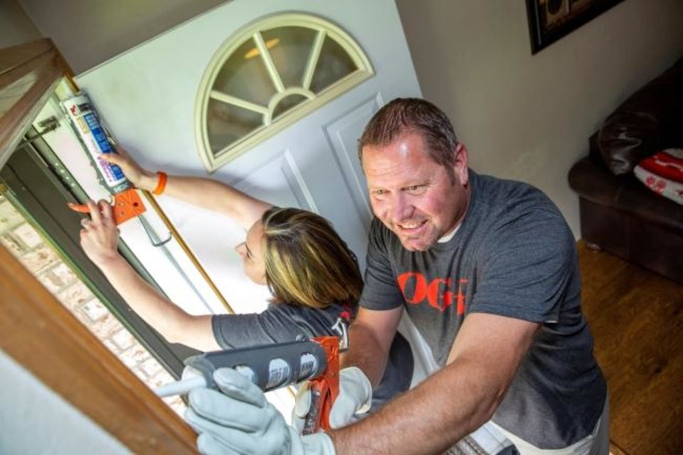 Photo -  OG&E volunteers Keith Erickson and Nicole Rhodes caulk around a door during the utility's Silver Energy Sweep initiative in Oklahoma City. [PROVIDED BY OG&E]
