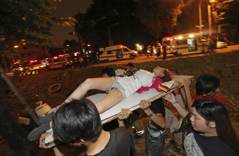 Photo - A victim in a gas explosion from an underground gas leak is carried from the rubble in a main street in Kaohsiung, Taiwan, early Friday, Aug. 1, 2014.  A massive gas leakage early Friday caused five explosions that killed several people and injured over 200 in the southern Taiwan port city of Kaohsiung. (AP Photo)  TAIWAN OUT