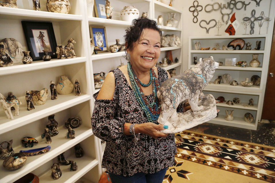 Photo -  Artist Yolanda White Antelope shows some of her horsehair pottery at her recently reopened Oklahoma Native Art and Jewelry gallery in the Stockyards in Oklahoma City. The gallery was one of the businesses that was forced to close in Stockyards City after a fire. [Photos by Paul Hellstern, The Oklahoman]
