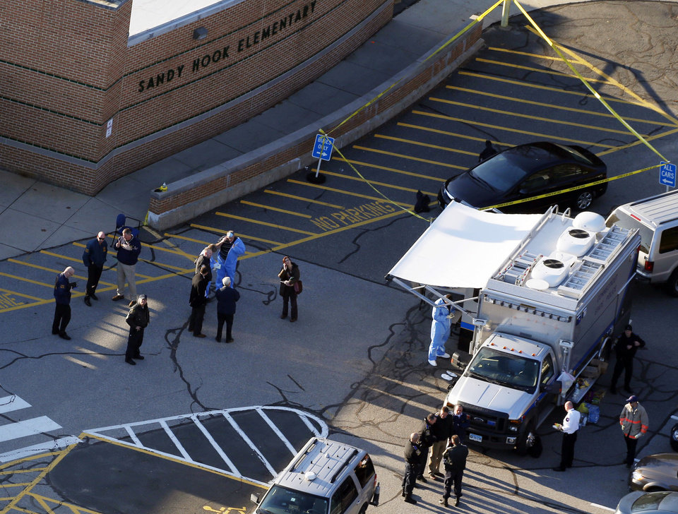 Photo - Officials are on the scene outside of Sandy Hook Elementary School in Newtown, Conn., where authorities say a gunman opened fire inside an elementary school in a shooting that left 27 people dead, including 20 children, Friday, Dec. 14, 2012. (AP Photo/Julio Cortez) ORG XMIT: CTJC104