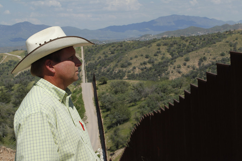 Photo - In this Friday, Aug. 10, 2012 photo, rancher Dan Bell, who owns a 35,000-acre cattle ranch along the border between the United States and Mexico, looks at the imposing border fence, in Nogales, Ariz. When Bell drives through his property, he speaks of the hurdles that the Border Patrol faces in his rolling green hills of oak and mesquite trees: The hours it takes to drive to some places, the wilderness areas that are generally off-limits to motorized vehicles, and the environmental reviews required to extend a dirt road. (AP Photo/Ross D. Franklin)