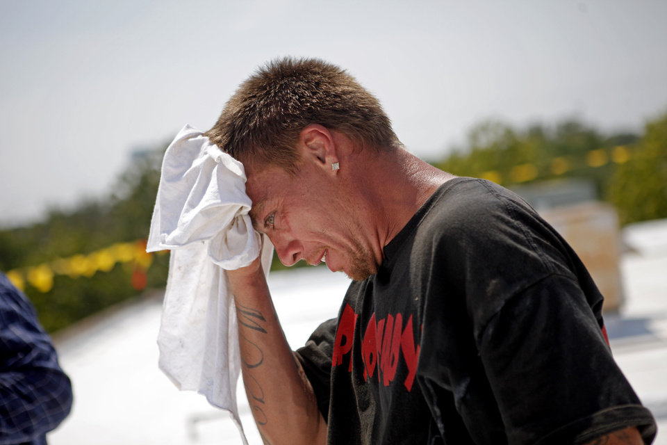 Nicholas Esparza wipes sweat off his face as he works on top of a roof in Oklahoma City, Friday, July 8, 2011. Photo by Bryan Terry, The Oklahoman
