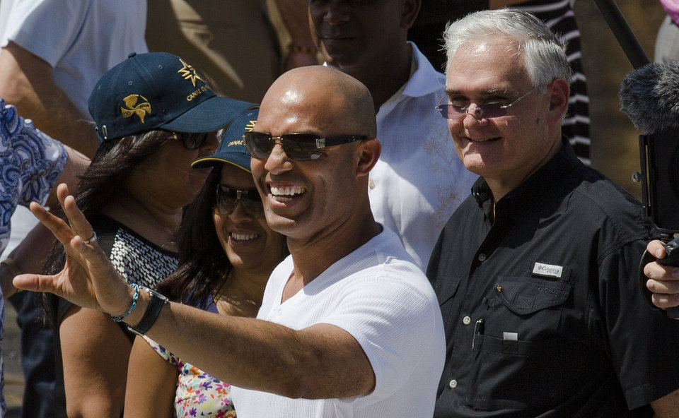 Photo - Mariano Rivera former New York Yankees baseball pitcher waves to the crowd, as Panama Canal Administrator Jorge Quijano, right, stands next to him during a visit to the Miraflores Locks at the Panama Canal in Panama City, Friday, March  14, 2014. The New York Yankees and the Miami Marlins will play on March 15-16, in the