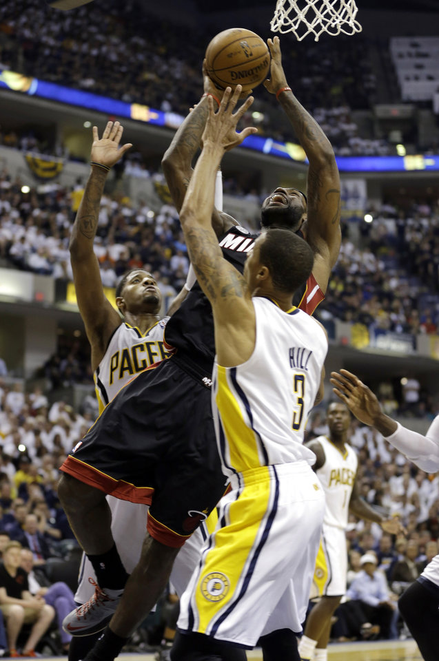 Miami Heat's LeBron James, center, puts up a shot against Indiana Pacers' Paul George, left, and George Hill during the first half of Game 3 of the NBA Eastern Conference basketball finals in Indianapolis, Sunday, May 26, 2013. (AP Photo/Nam H. Huh)