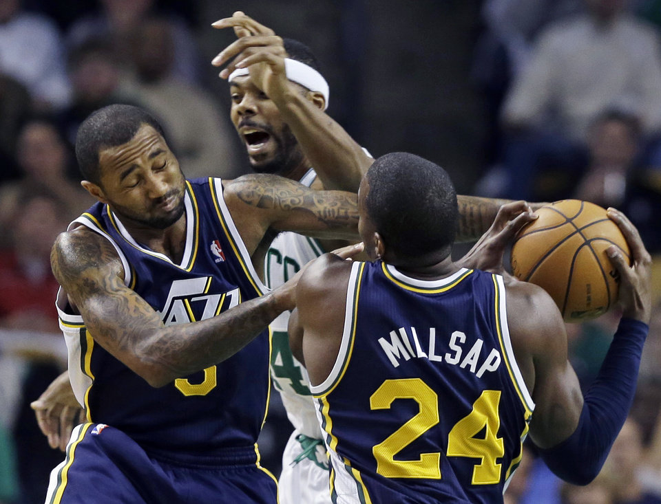 Utah Jazz power forward Paul Millsap (24) comes away with a loose ball as he and point guard Mo Williams, left, fight for it against Boston Celtics power forward Chris Wilcox, behind, during the first half of an NBA basketball game in Boston, Wednesday, Nov. 14, 2012. (AP Photo/Elise Amendola)
