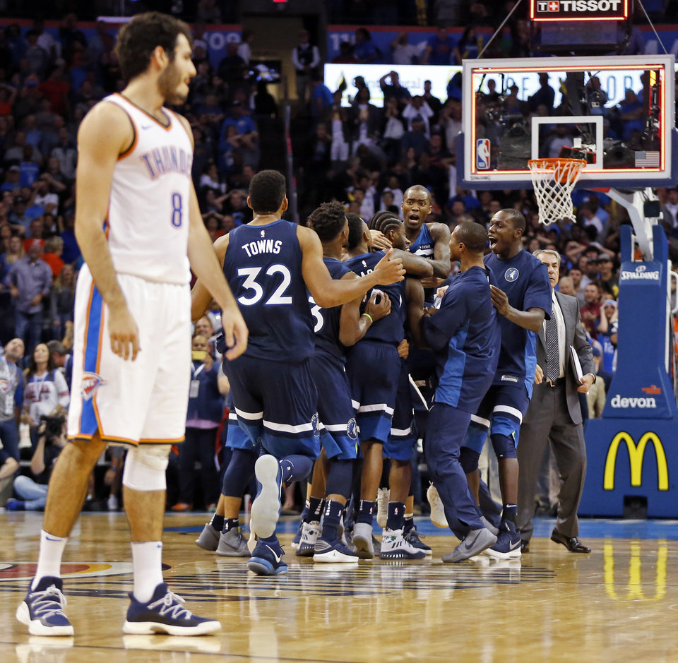 Photo - The Minnesota Timberwolves celebrate after Andrew Wiggins (22) made a game-winning shot as time expired as Oklahoma City's Alex Abrines (8) walks off the court at the end of an NBA basketball game between the Oklahoma City Thunder and the Minnesota Timberwolves at Chesapeake Energy Arena in Oklahoma City, Sunday, Oct. 22, 2017. Minnesota won 115-113. Photo by Nate Billings, The Oklahoman