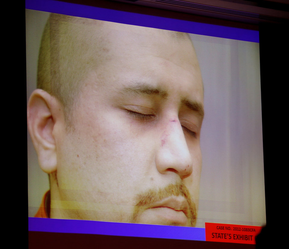 Photo - State exhibit photos, including this of George Zimmerman on the night of the Trayvon Martin shooting, are projected on a video screen in court during the 15th day of Zimmerman's trial in Seminole circuit court, in Sanford, Fla., Friday, June 28, 2013.  Zimmerman has been charged with second-degree murder for the 2012 shooting death of Trayvon Martin. (AP Photo/Orlando Sentinel, Joe Burbank, Pool)