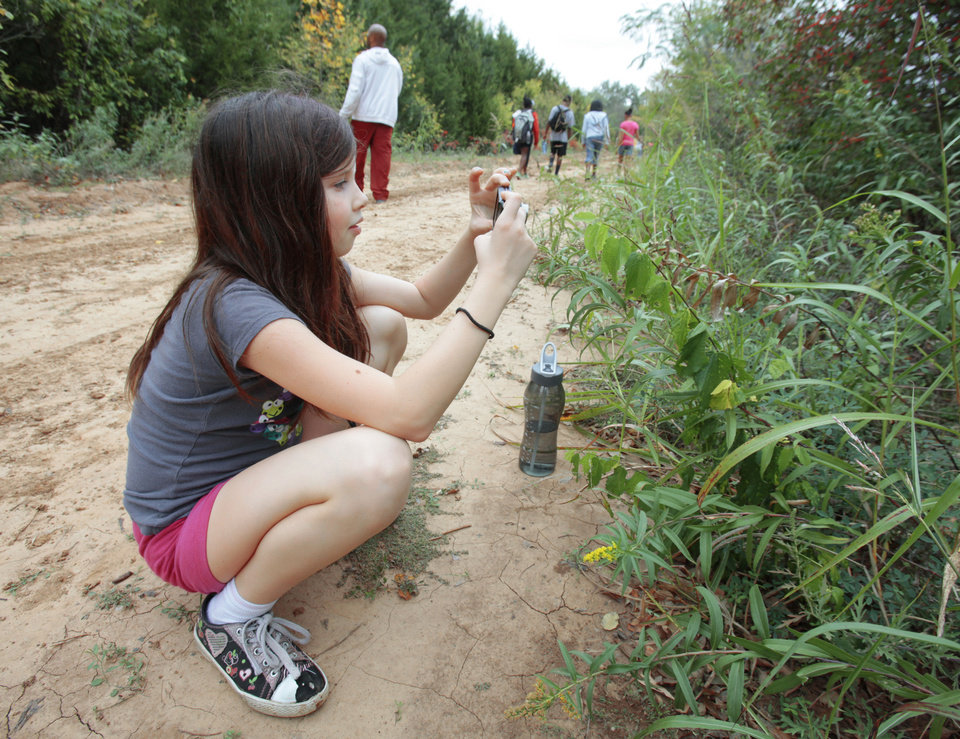 "Basil, 10, takes photos during an outing with The Boys and Girls Club's new program called ""Parks in Focus"" at the Stinchcomb Wildlife Refuge. Photo By David McDaniel/The Oklahoman <strong>David McDaniel - The Oklahoman</strong>"