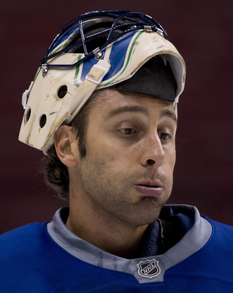 Vancouver Canucks goalie  Roberto Luongo pauses at NHL hockey training camp at Rogers Arena in Vancouver, British Columbia, Tuesday, Jan. , 15, 2013. (AP Photo/The Canadian Press, Jonathan Hayward)