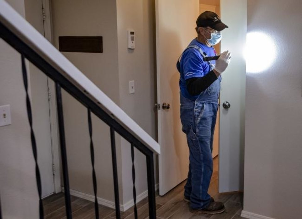 Photo -  Phillip Culp, of K9 Termite Finders, inspects the closet of a home at 9905 Hefner Village Place. [CHRIS LANDSBERGER/THE OKLAHOMAN]